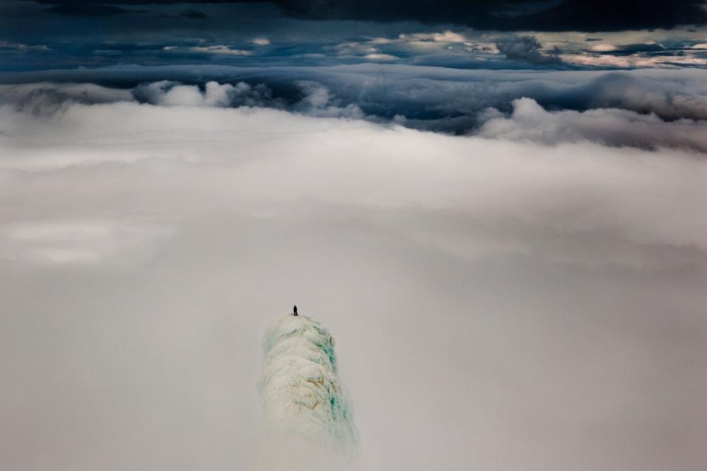 Альпинист стоит на вершине горы в Исландии